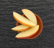 Red apple slices in a small clay bowl Stock Images