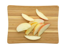 Red apple slices on a wood cutting board Royalty Free Stock Photos