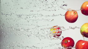 Red apple with splashes of water. On a white background, slow motion stock video footage