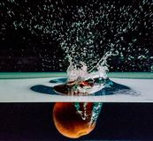 Red apple splashing into water Royalty Free Stock Image