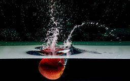 Red apple splashing into water Royalty Free Stock Images