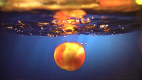 The red Apple in the spray falls into the water on a gray background, slow motion. Orange falls into the water.