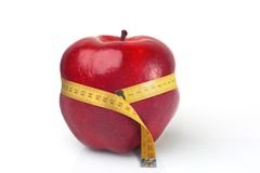 Red Apple Squeezed By Tape Measure Stock Photo