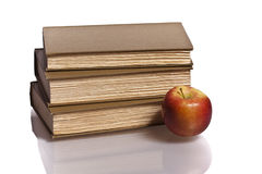 Red apple stack of books. Hardcover books reflection white background red apple Stock Photo