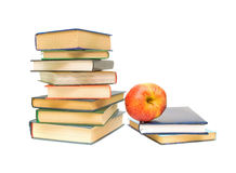Red apple and stack of books on white background. Ripe red apple and stack of books closeup on white background Royalty Free Stock Photography