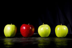 Red apple stands out. Red apple standing out in a row of green apples Stock Photo