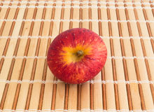 Red apple on strips of wood, seen from above. A small red apple cracked on strips of wood, seen from above Royalty Free Stock Photography