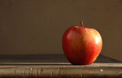 Red apple on table. With side light. Wall background Royalty Free Stock Photo