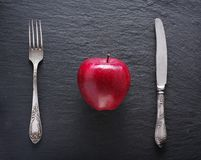 Red apple and table settings on a dark background. Stock Images