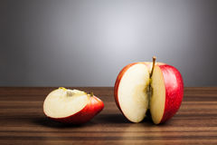 Red apple  on table with sliced piece, gray background Stock Photo