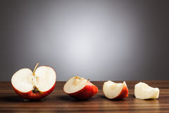 Red apple on table with sliced pieces, gray background Royalty Free Stock Photo