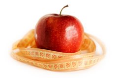 Red apple and tape measure. On the white background Royalty Free Stock Photos