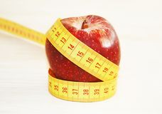 Red apple with tape measure - weight loss - diet concept Royalty Free Stock Photos