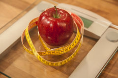 Red apple and tape measure on weight scale. Stock Photography