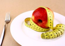 Red apple and tape measure on white plate with fork Royalty Free Stock Image