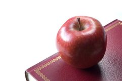Red apple for teacher resting on a book Royalty Free Stock Images
