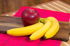 Red apple and three bananas on wooden surface Stock Image
