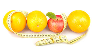 Red apple between three oranges and measuring tape. Red apple with green leaf between three oranges and measuring tape isolated on white background Stock Photography