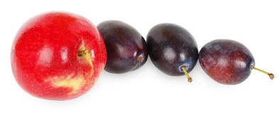 Red apple and three plums Stock Photo