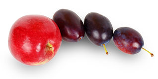 Red apple and three plums Royalty Free Stock Photo