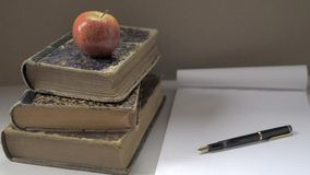 Red apple on three stacked books, a fountain pen and a notebook. stock video