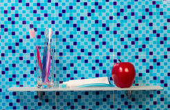 Red apple with toothpaste and brush on shelf Royalty Free Stock Photography