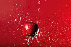 Red apple under splashing on a red background Stock Photo