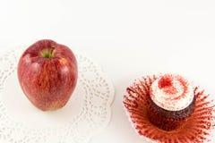 Red apple vs red velvet cupcake Royalty Free Stock Image