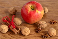 Red apple, walnuts, cinnamon and star anise Royalty Free Stock Photography