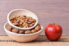 Red apple and walnuts on wooden dishes Stock Image