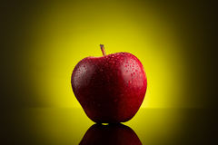 Red apple with water drops on yellow background Stock Images
