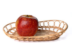 Red apple on wattled plate isolated Royalty Free Stock Photography