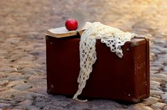 Red Apple, white handkerchief and old book open on the old suitcase standing on the cobblestones. With sun spots at sunset Stock Photography