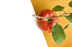 Red apple and white paper on woden table. Stock Photos