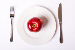 Red apple on white plate Royalty Free Stock Photos