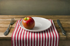 Red apple on white plate Stock Photo