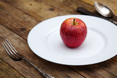 Red apple on a white plate Stock Images