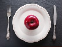 Red apple on a white plate. Royalty Free Stock Photo