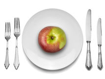 Red apple on white plate with knife and fork, Royalty Free Stock Photos