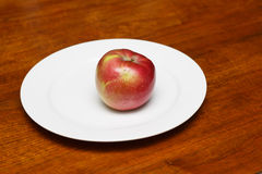 Red Apple on White Plate Stock Photography
