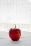 Red apple. On a white window sill. copy space Stock Images