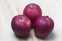 Red apple on wooden background. 3 apple in a wooden wood Royalty Free Stock Photos