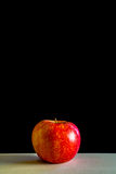 Red apple an a wooden board with black background. Red apple on a wooden board with black background, with empty upper half, copyspace, health related still life Stock Image
