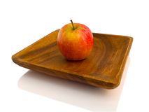 Red apple on wooden plate Royalty Free Stock Photos
