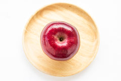 Red apple in wooden plate on white background. Royalty Free Stock Images