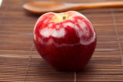 Red apple and a wooden spoon on a bamboo mat Stock Images