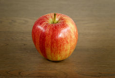 Red apple on a wooden substrate. Red and yellow striped apple on wooden substrate Stock Photography