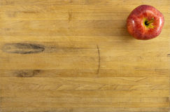 Red Apple on Worn Cutting Board Stock Photo
