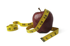 Keeping diet. Red apple wrapped in measuring tape isolated on white background. Symbol of healthy eating, loosing weight and keeping a healthy diet Royalty Free Stock Image