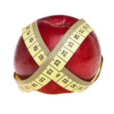 Red apple wrapped with yellow measurement tape. Royalty Free Stock Image